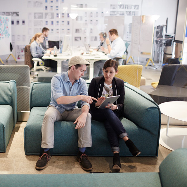 Two people sitting on a couch, looking at a tablet.