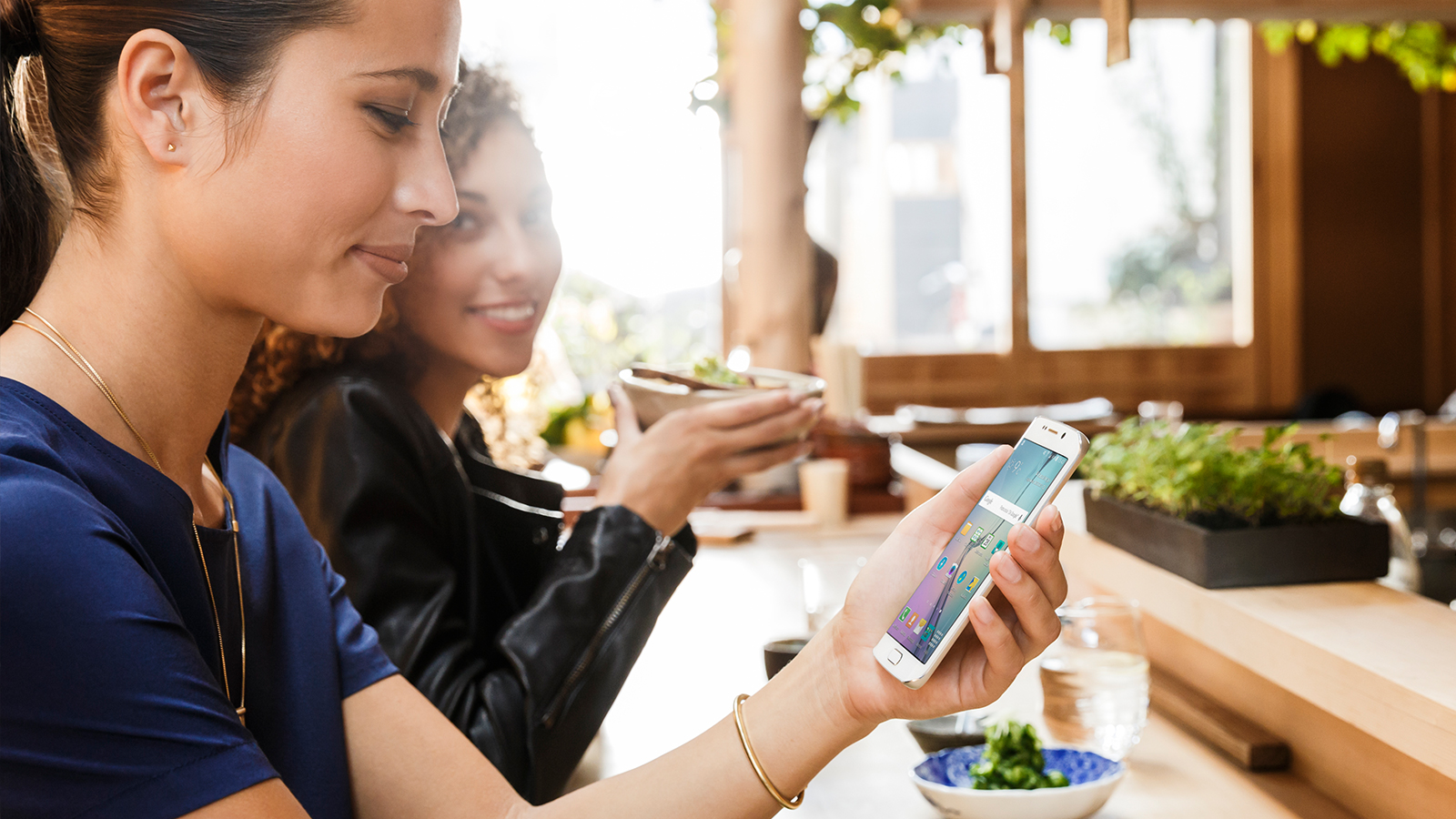 Women at table looking at phone