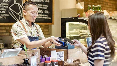Women paying through mobilephone over electronic reader at cafe counter