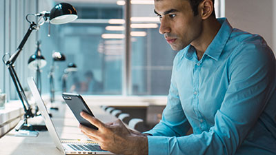 Young man using phone while working on laptop
