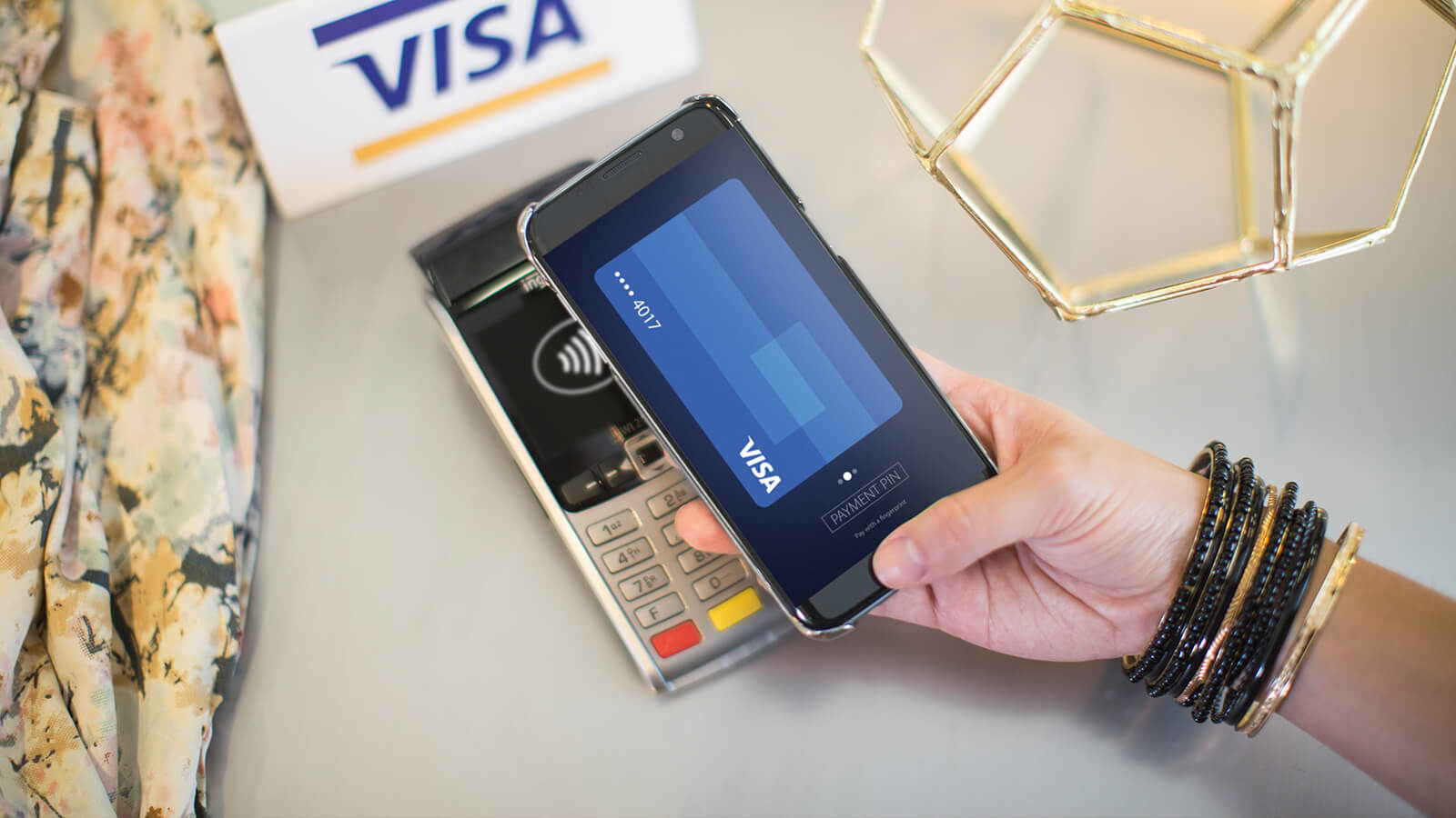 A closeup of a shopper using the Visa card on her phone to make a contactless payment at a terminal.