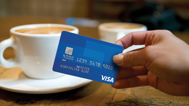 Woman's hand holding credit card with two coffee's on the table.